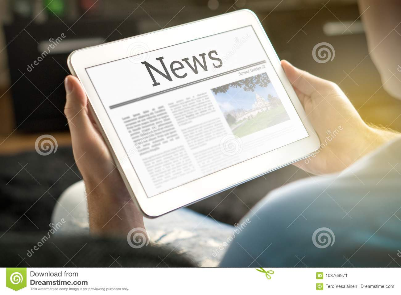 Man reading the news on tablet at home.