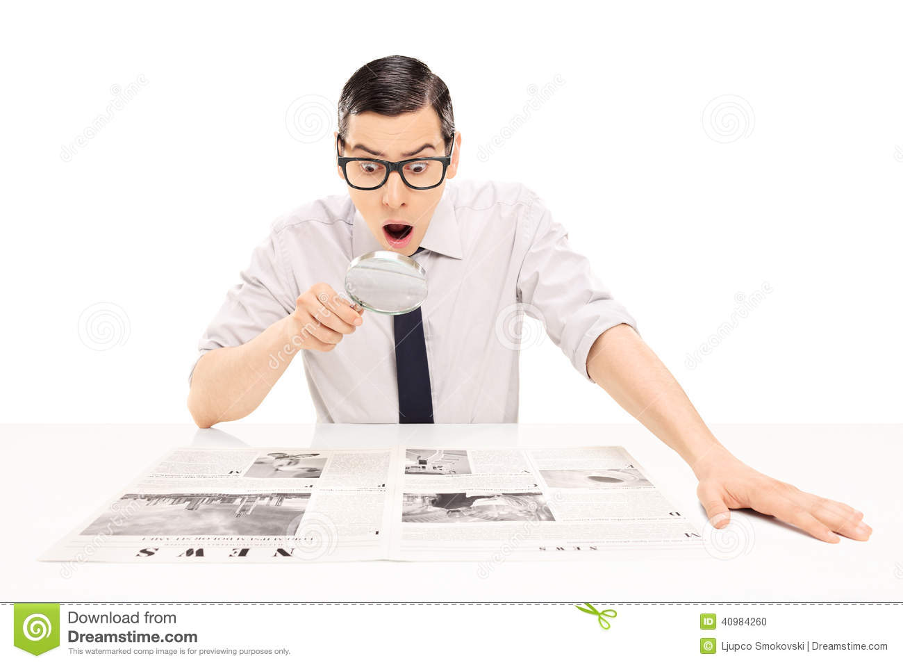 reading newspaper with magnifying glass stock photo