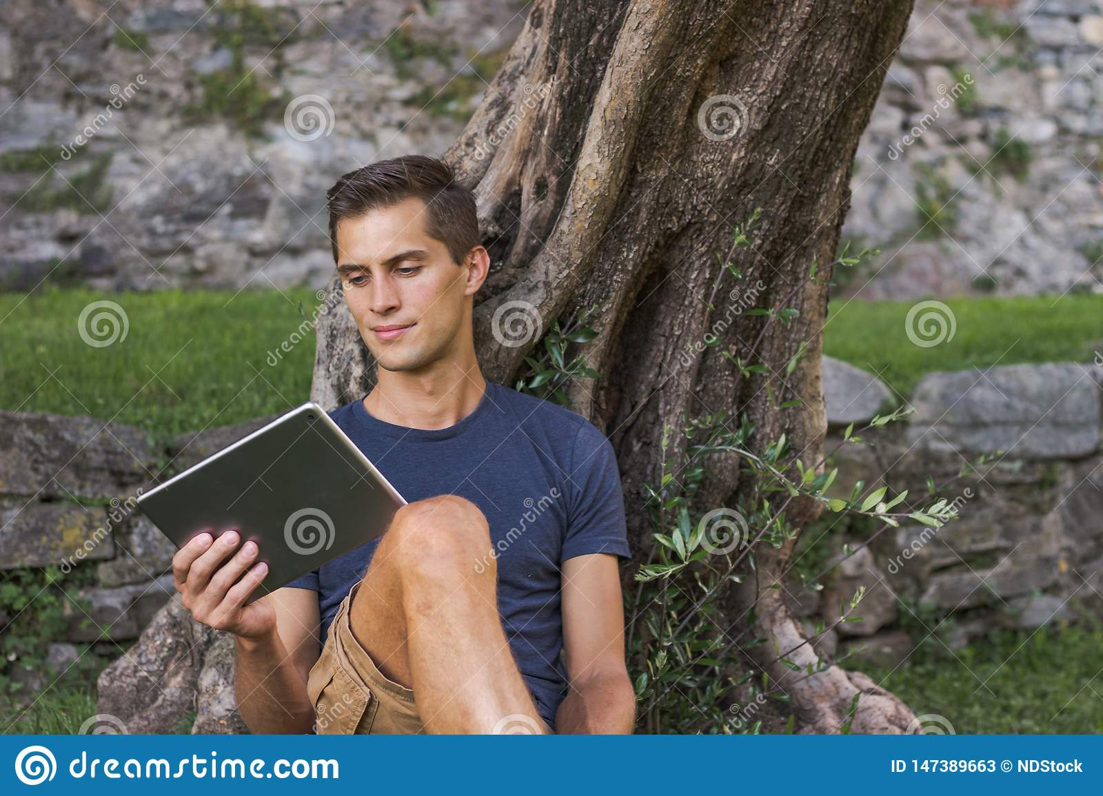Man reading tablet and enjoy rest in a park under tree