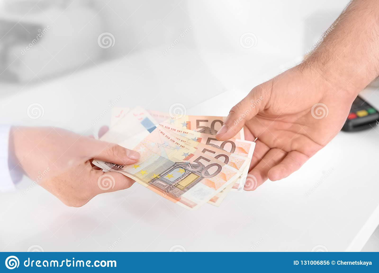 Man Receiving Money From Teller At Cash Department Stock Photo