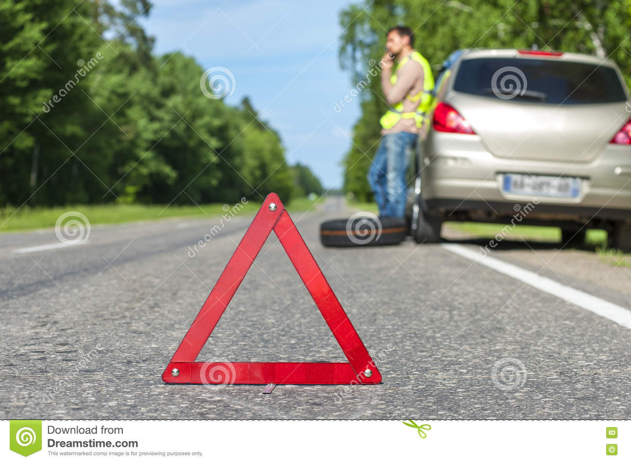 Man in reflective vest calling to a car assistance after breakdown