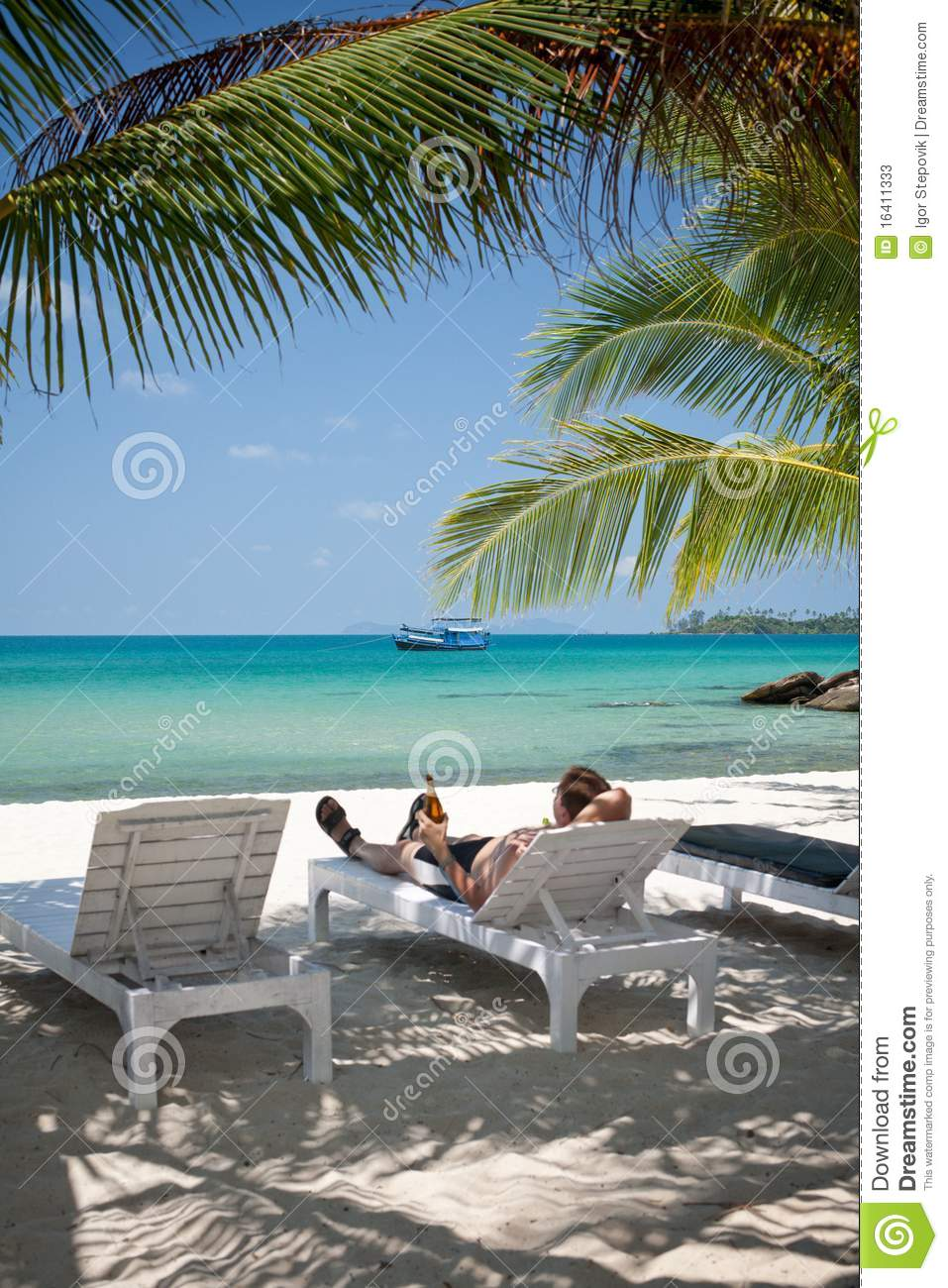 Man Relaxing With Beer In Shadows Under Palm Trees Stock