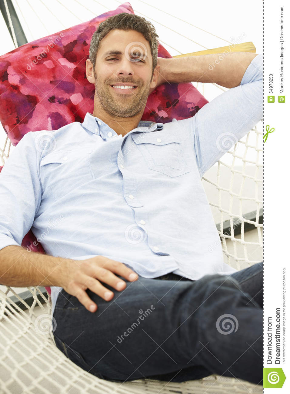 Man Relaxing In Garden Hammock