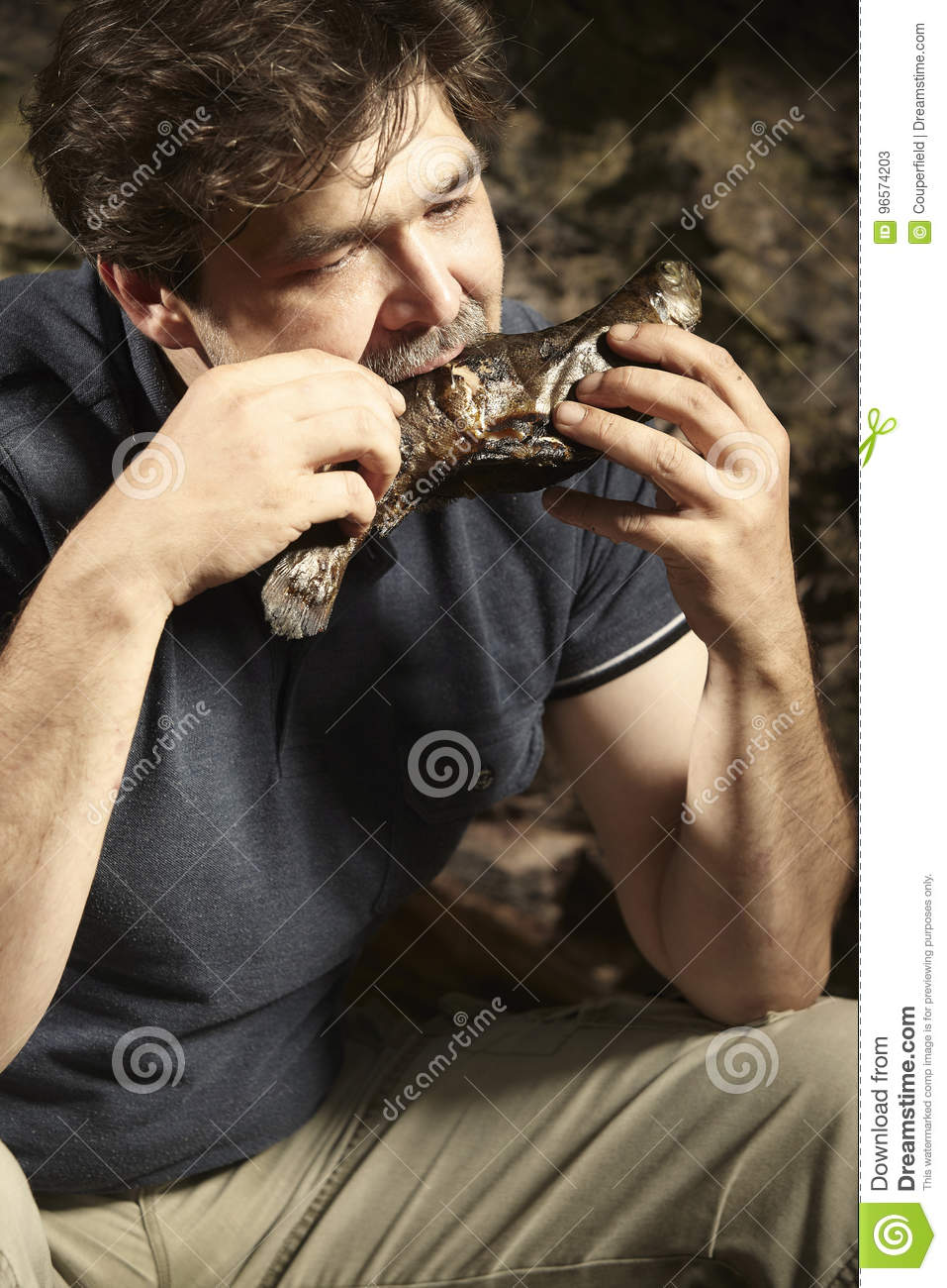 Man relaxing in wilderness and eating hunted fish
