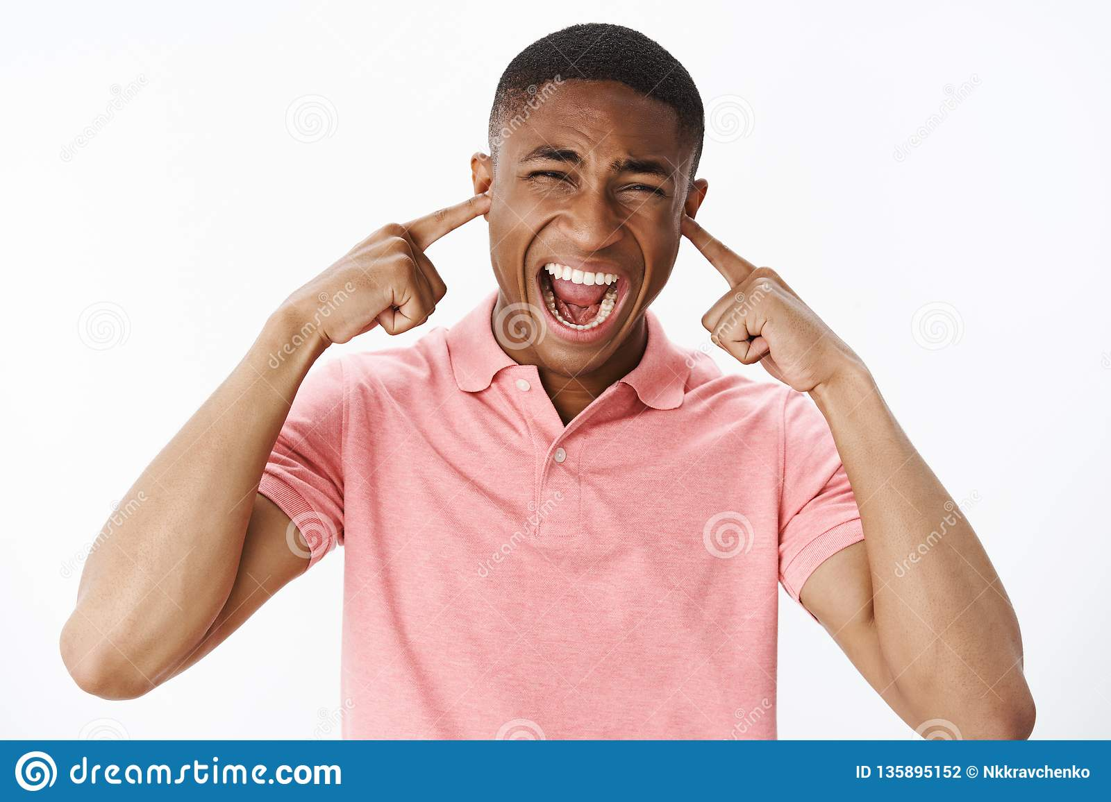 Man releasing stress cannot handle town noise. Displeased and fed up intense african american guy closing ears and