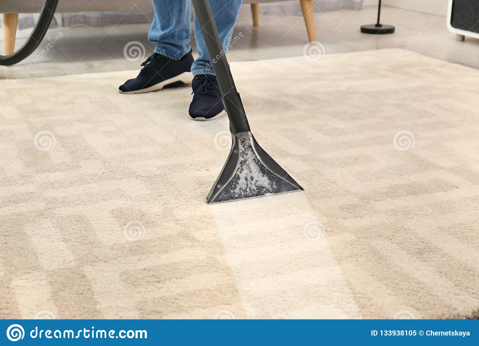 Man removing dirt from carpet with vacuum cleaner