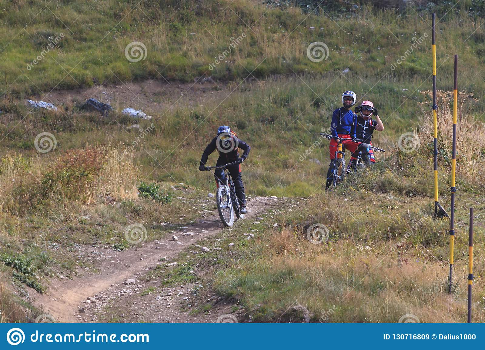 Man riding mountain bicycle downhill and two friends watching him