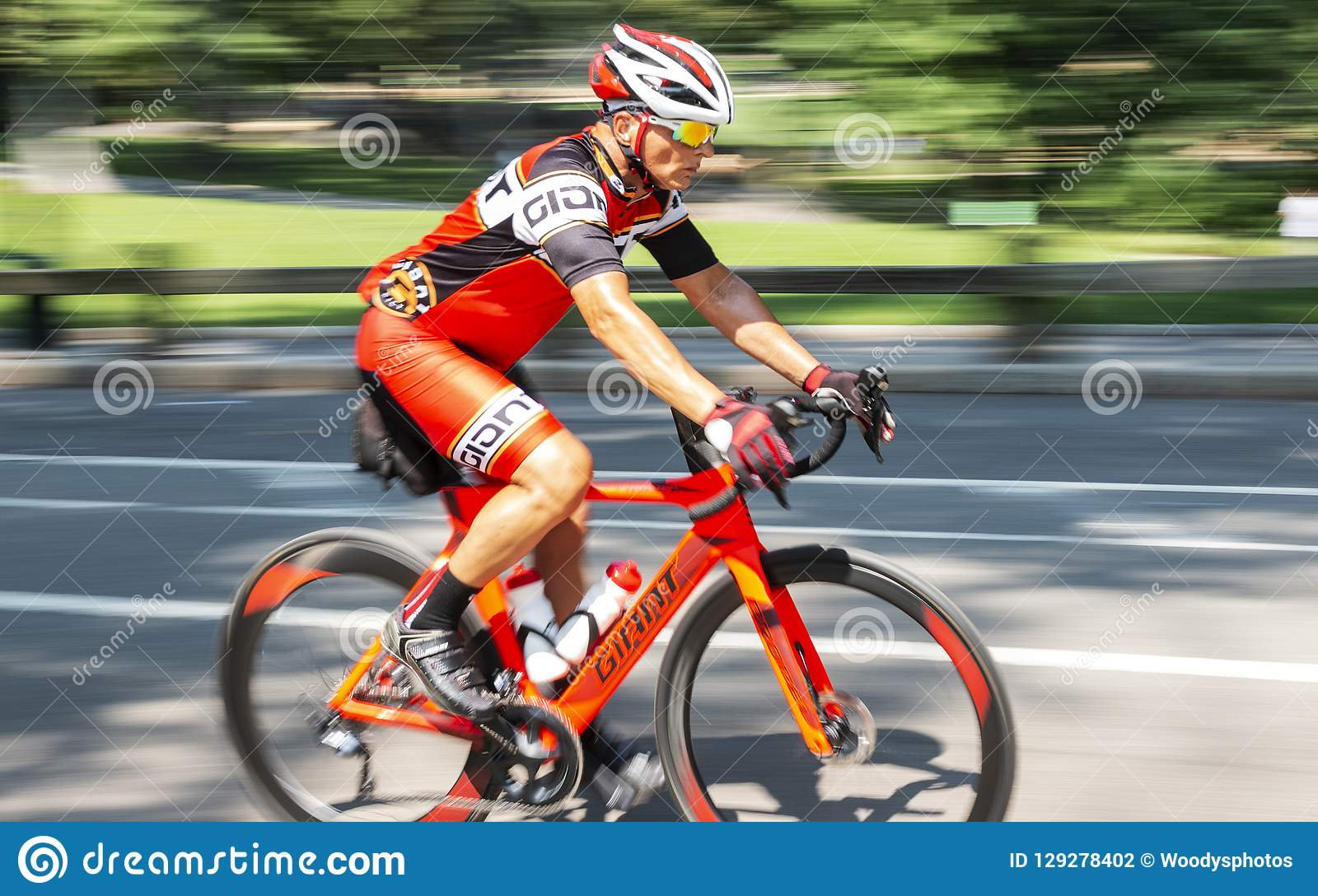 Man Riding Orange Racing Bike On Road Blurred Background Editorial