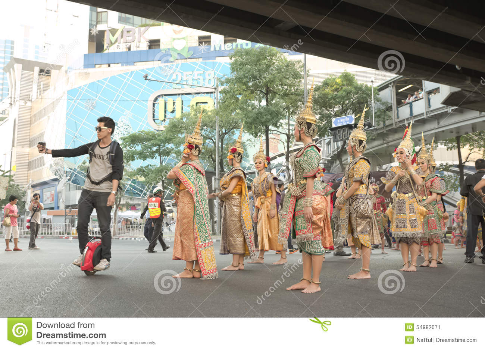 Man ridningenhjulingen som tar selfie med gruppen av thailändska traditionella dansare