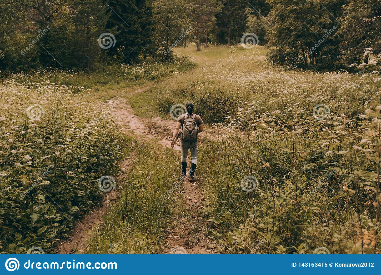 A man in rubber boots walks back through a flower meadow