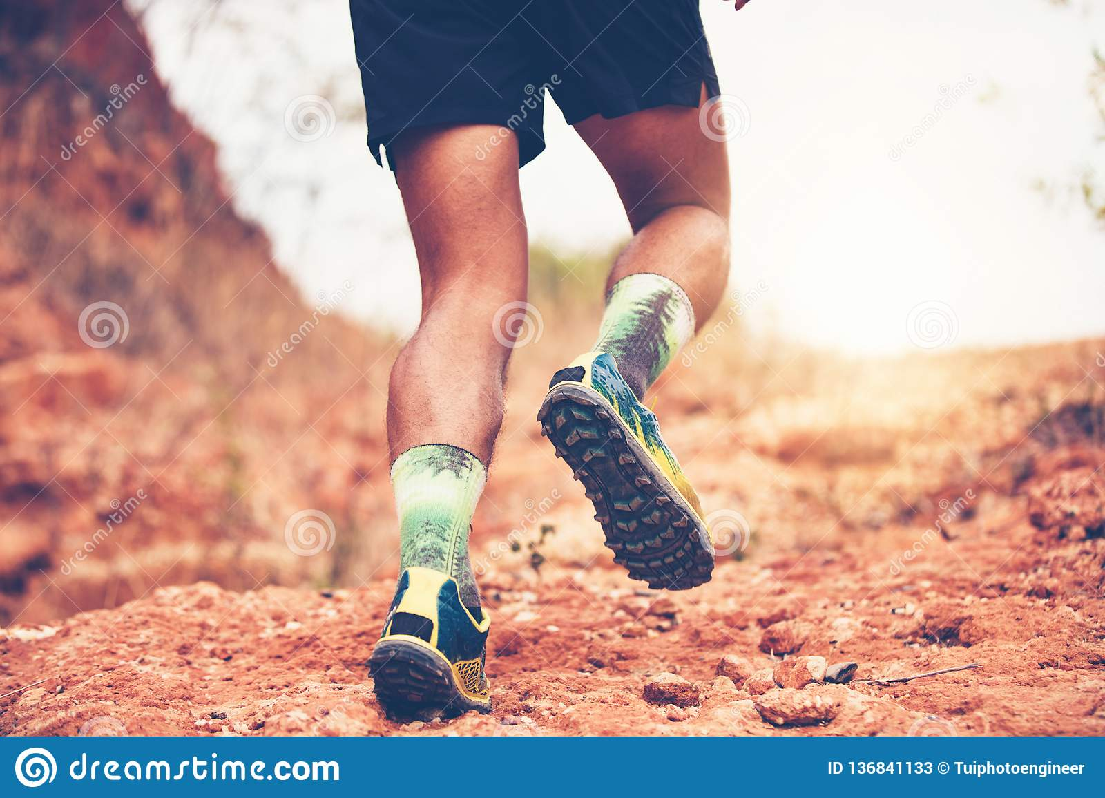 A man Runner of Trail . and Close up of an athlete`s feet wearing sports shoes for trail running in the mountains