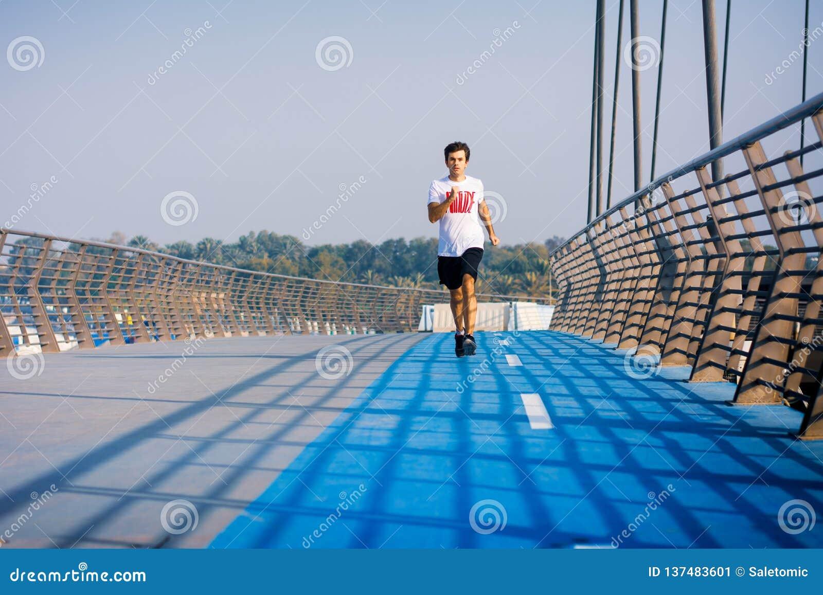 Man running on the bridge on a sunny day
