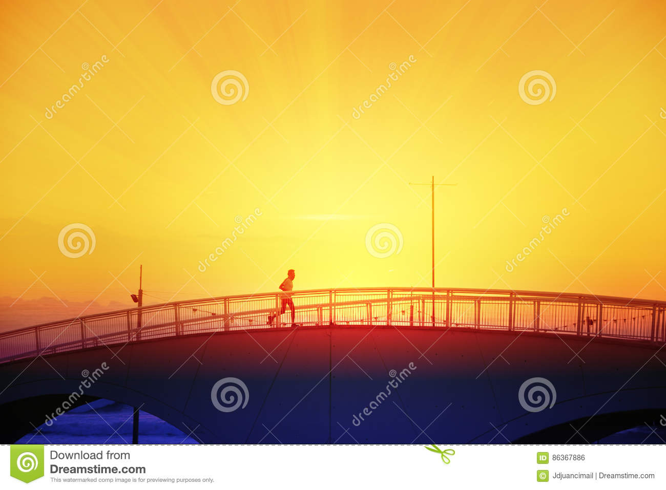 Man running crossing a bridge next to the beack at sunset.