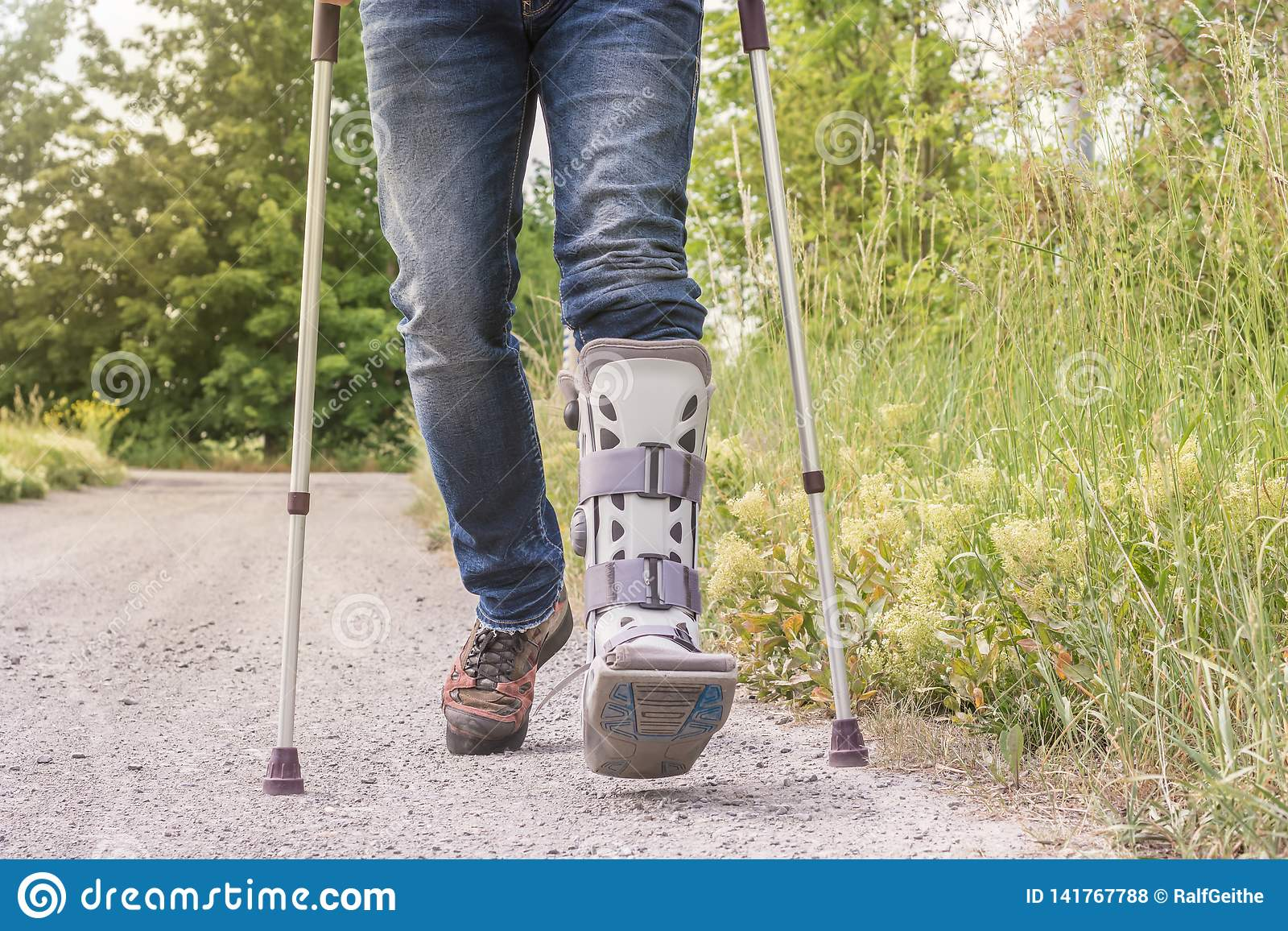 Man is running with an orthosis and walking aids on a dirt road