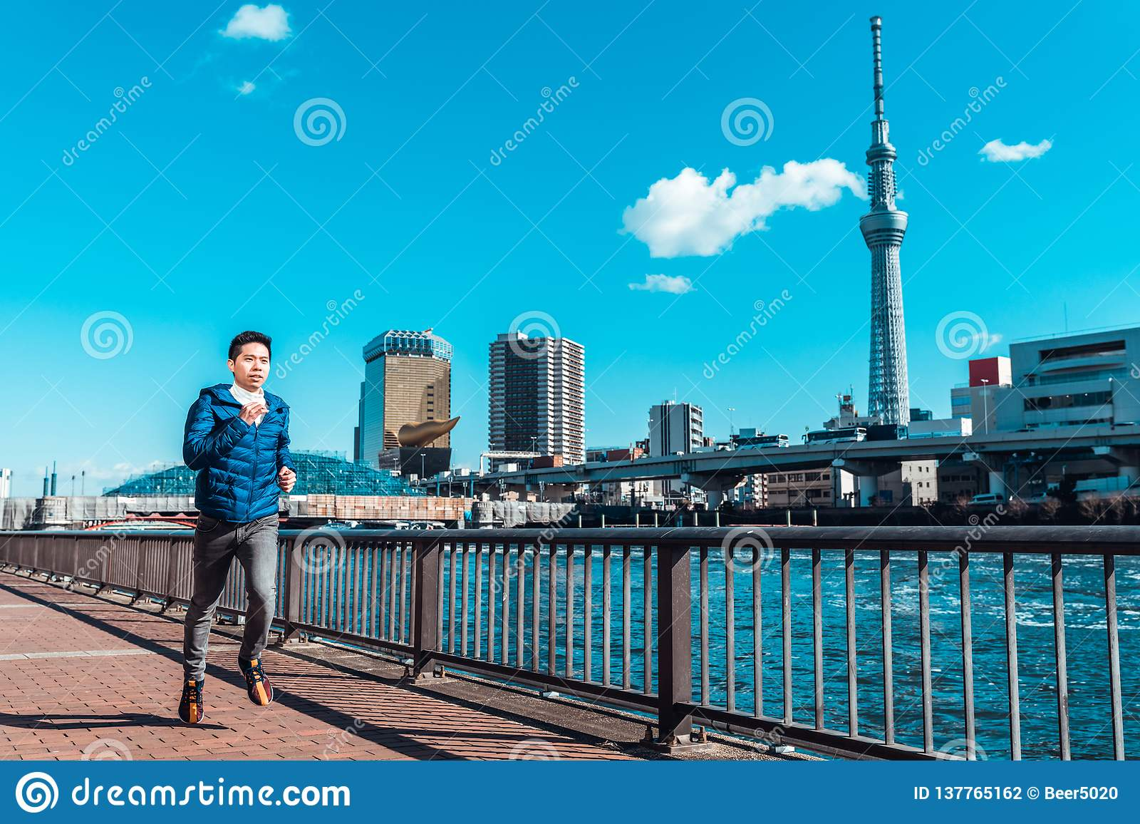Man running by Sumida river, Tokyo Skytree in background. Sport training, healthy lifestyle, or Tokyo 2020 summer Olympic concept