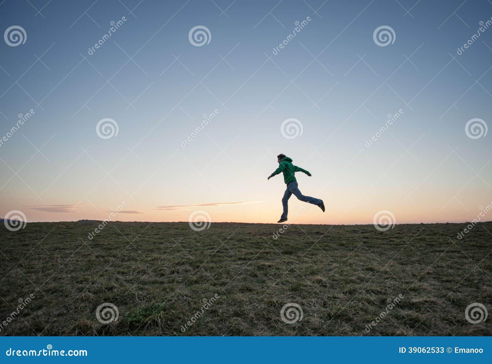 Man running in sunset sky on hill