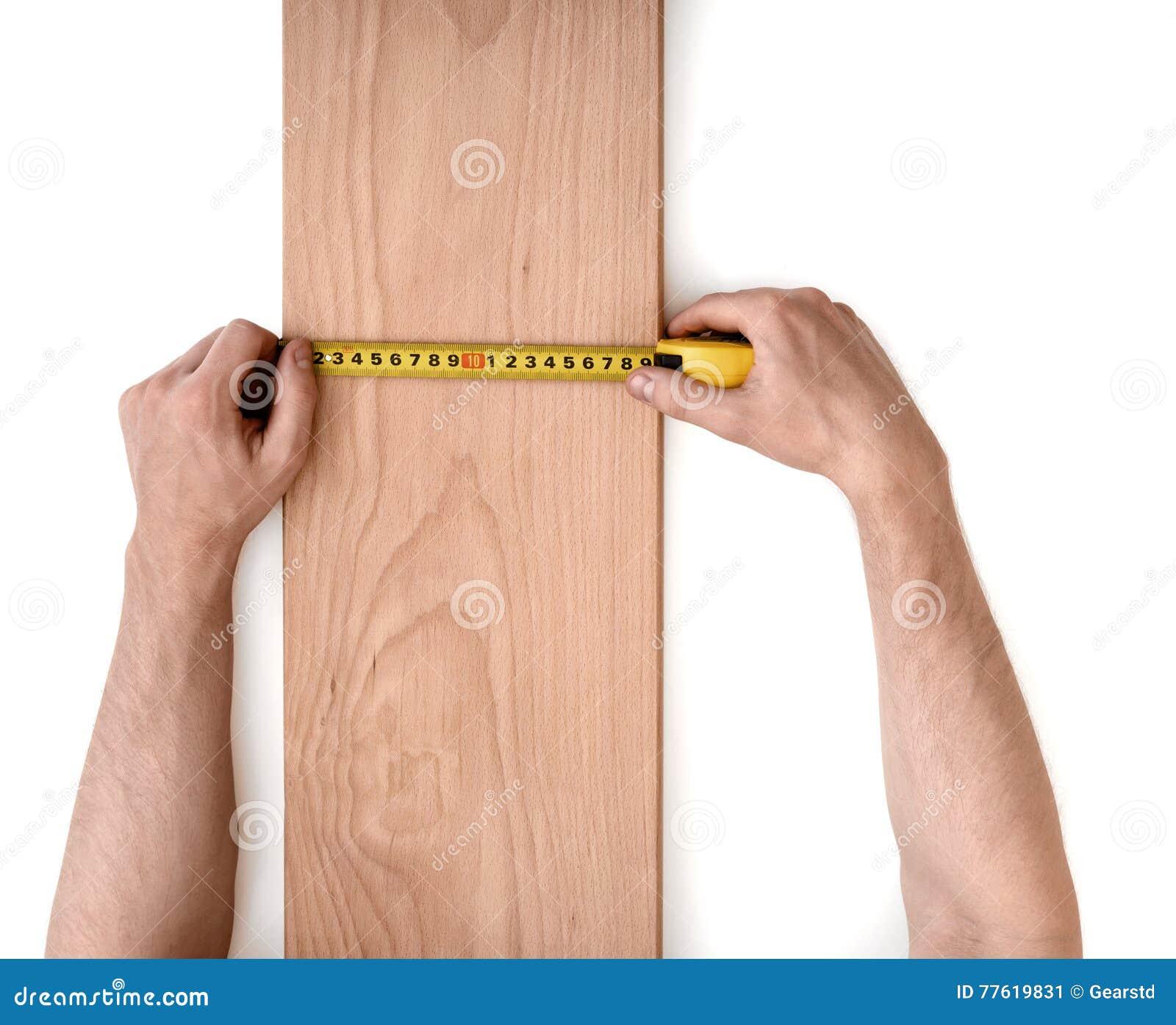 Man& x27; s da el tablón de madera de medición con una línea de la cinta aislada en el fondo blanco