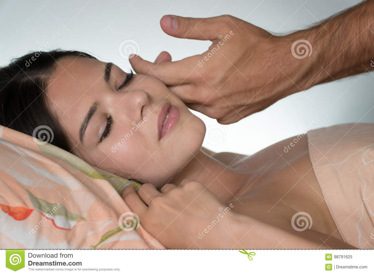 A man`s hand caresses the girl`s face in the morning. Morning awakening. Back of a blurred white background