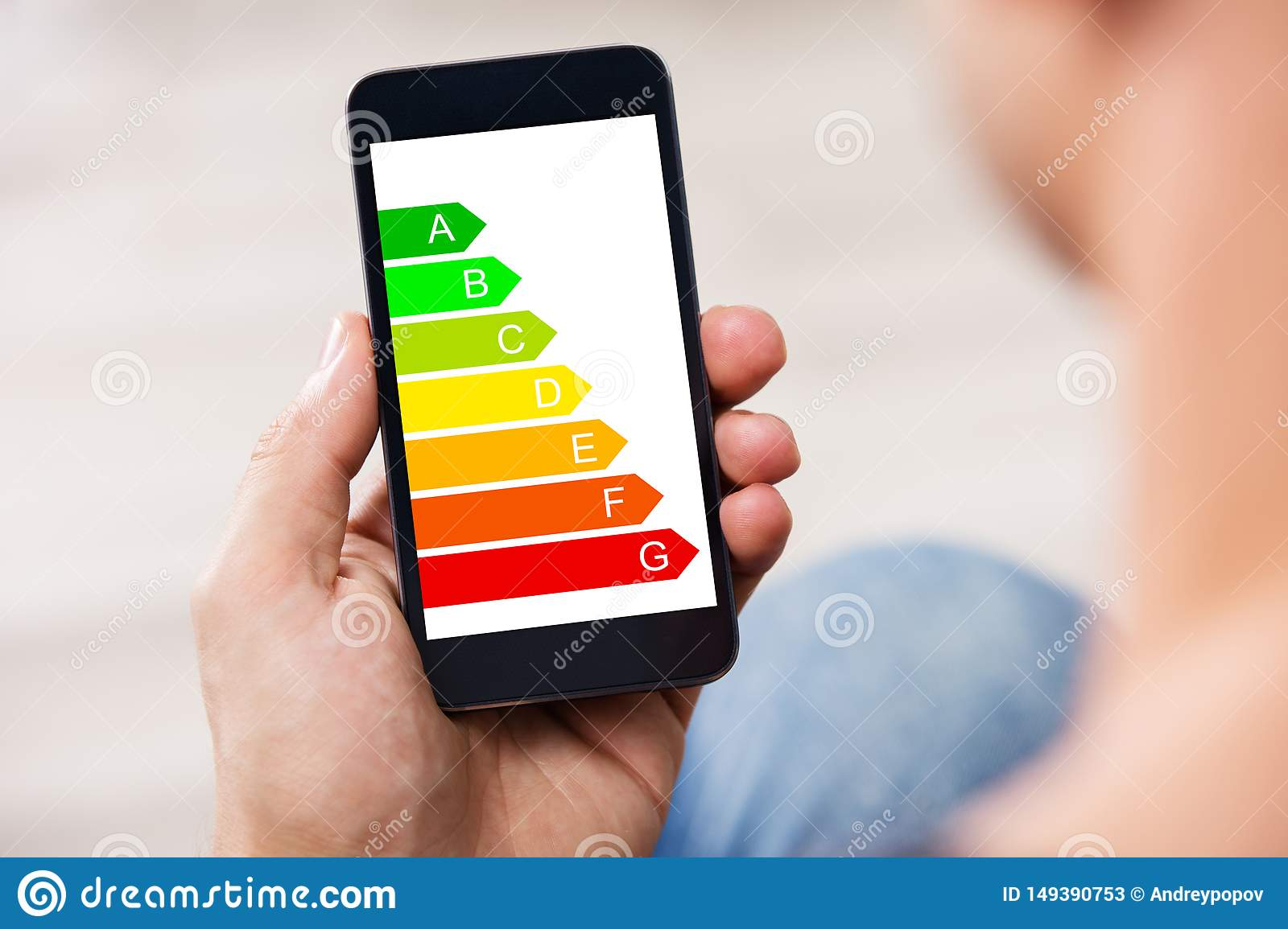 Man Holding Cellphone With Energy Efficiency Chart On Screen