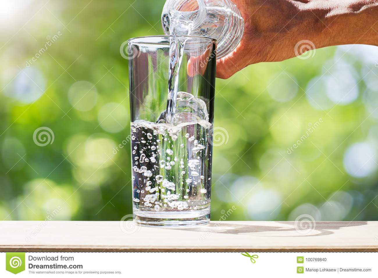 Man`s hand holding drinking water bottle water and pouring water into glass on wooden tabletop on blurred green bokeh background