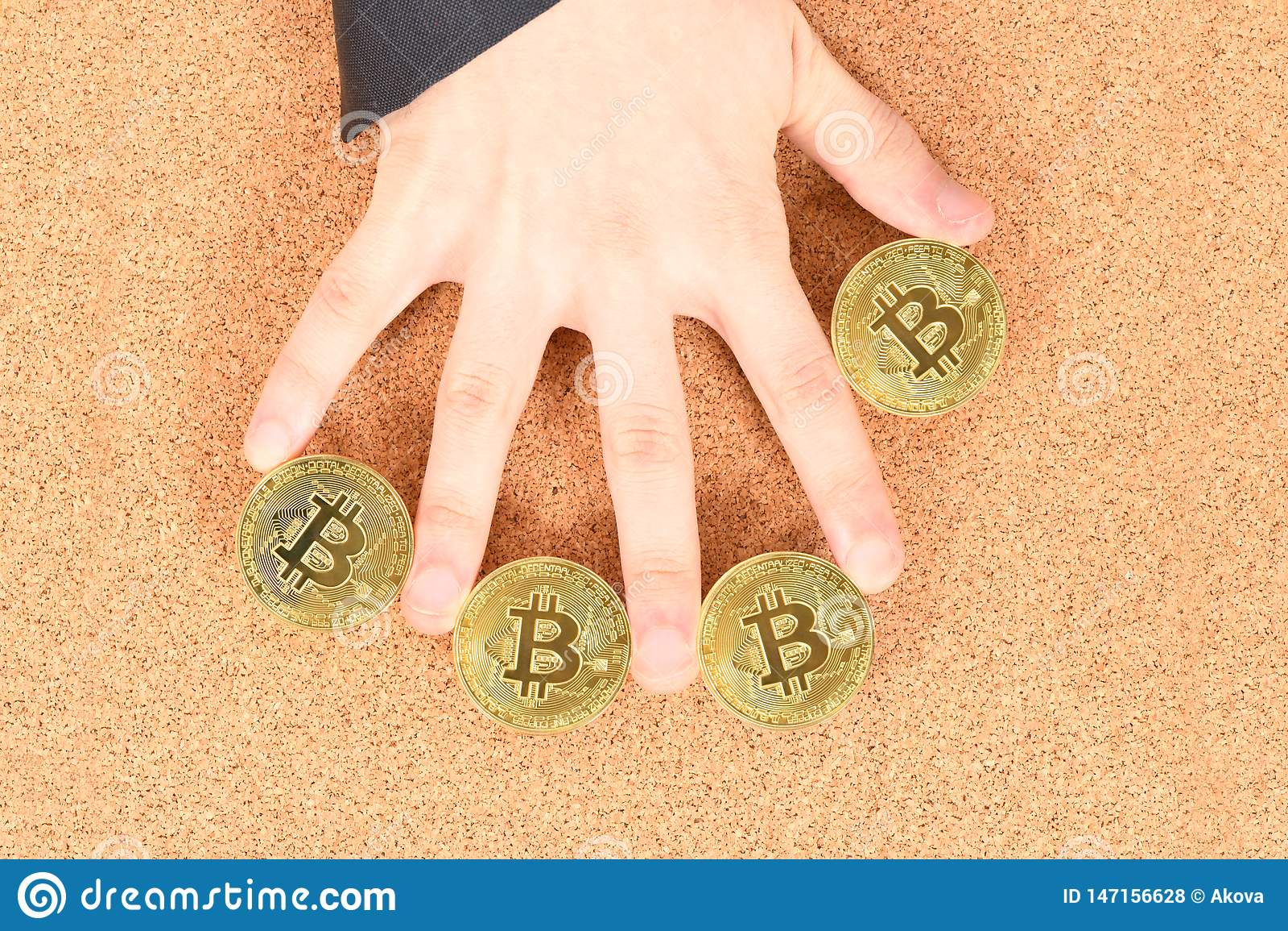 Man`s hand holding golden Bitcoin on brown textured cork background