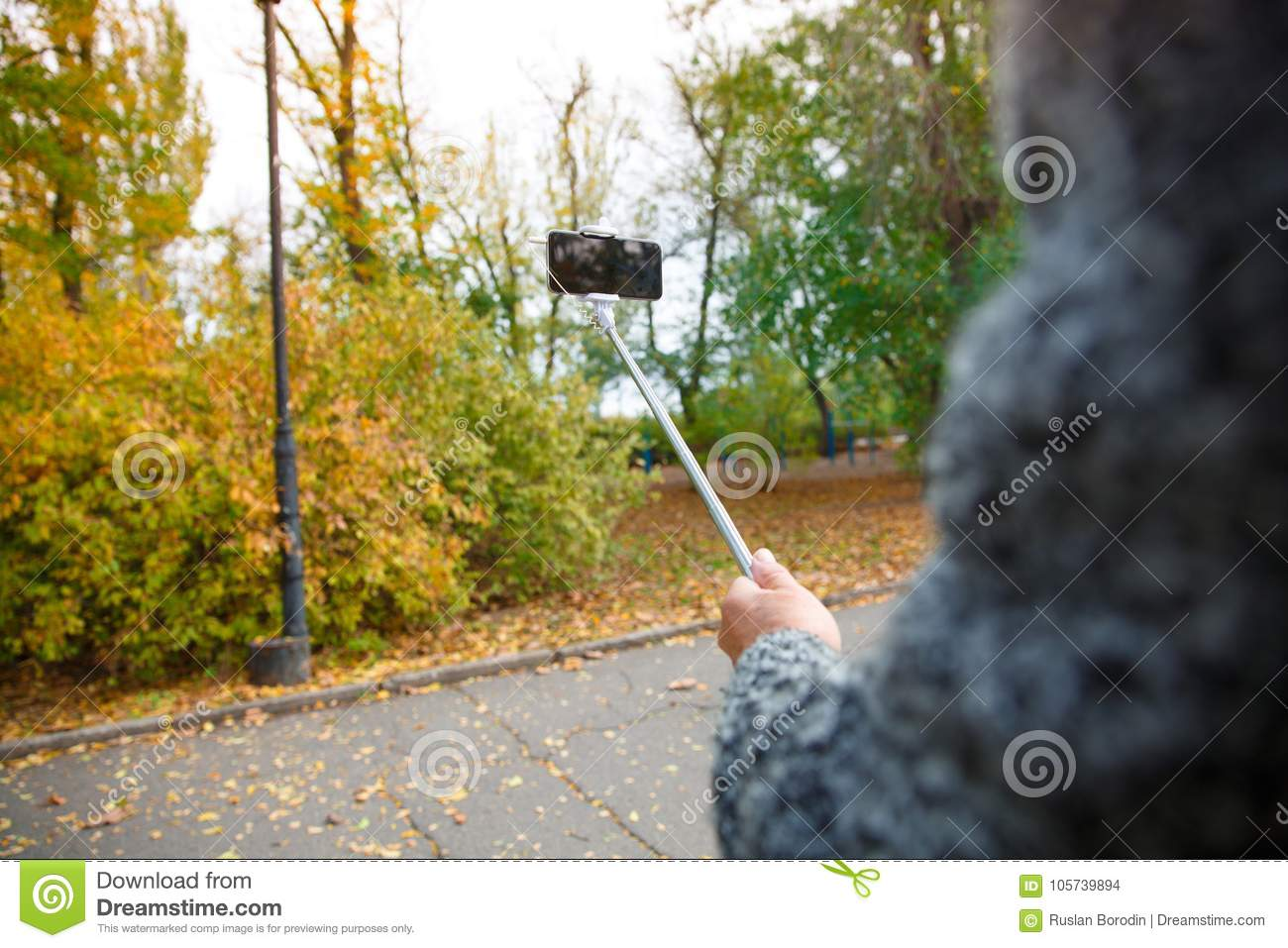 A man`s hand holding a mobile phone with a monopod in a warm park.