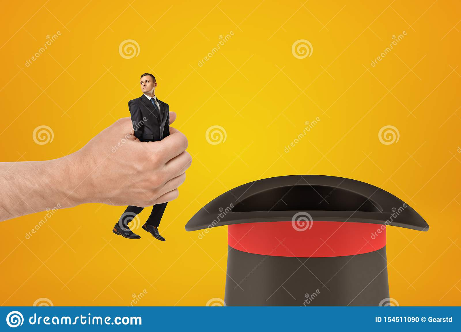 Man`s hand holding tiny businessman and putting him in black top-hat on amber background with some copy space above the