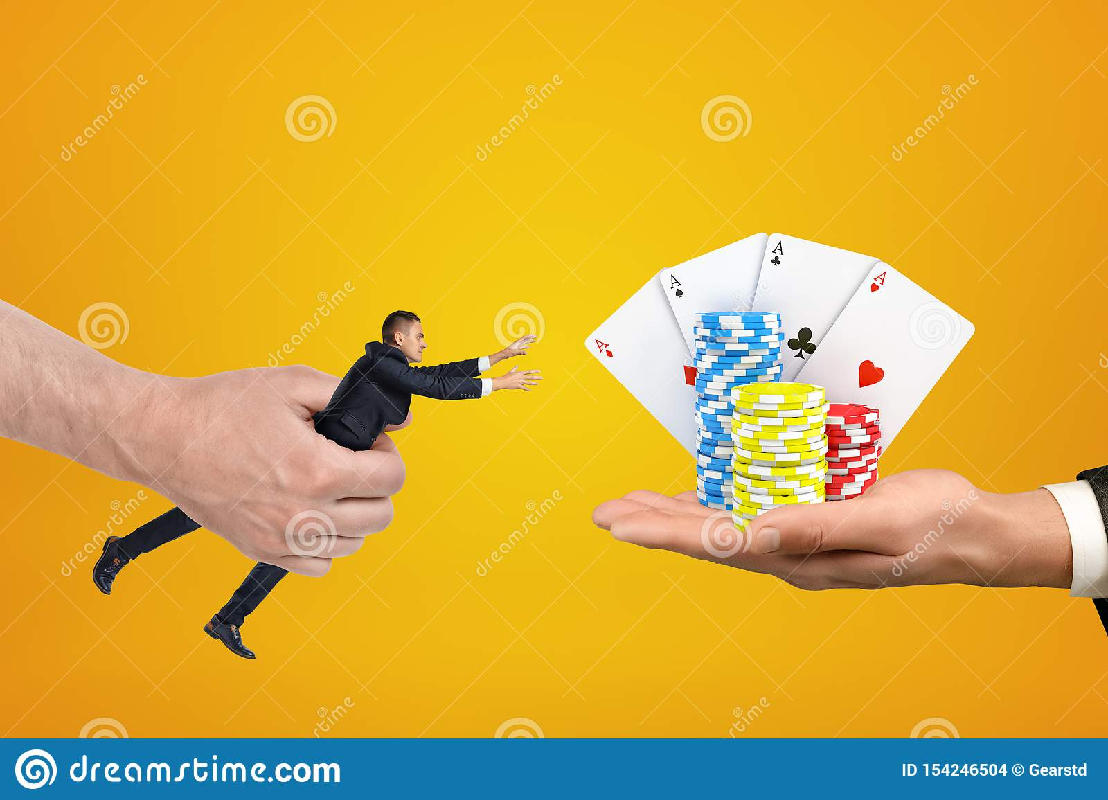 Man`s hand holding tiny businessman who is reaching out with both hands for cards and chips on another man`s palm on