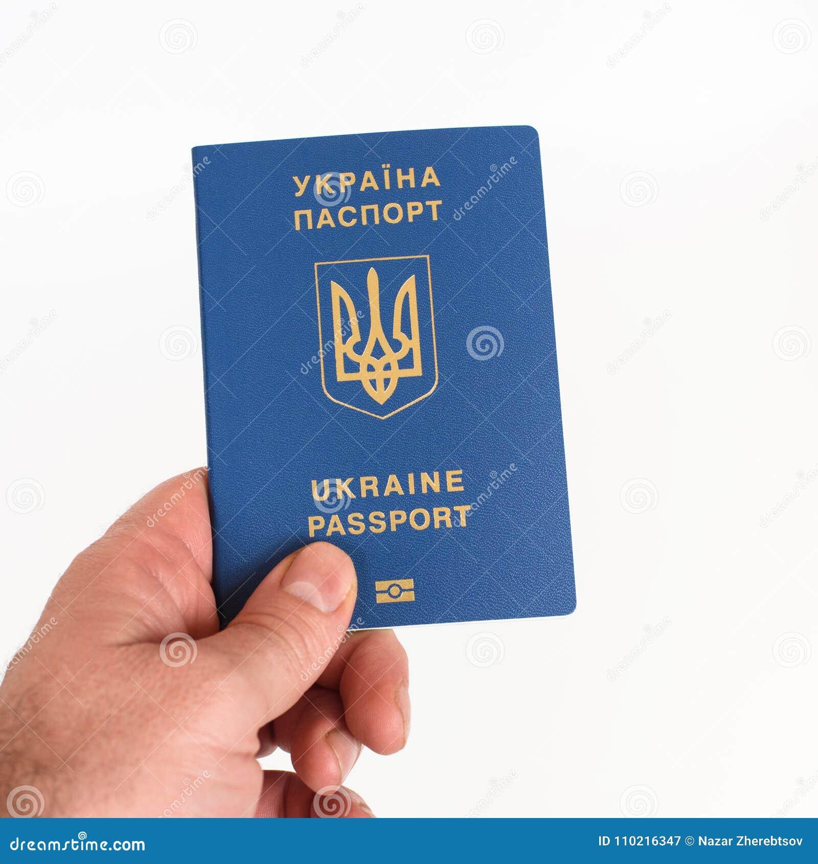 Man`s Hand holding Ukrainian biometric passport isolated on white background