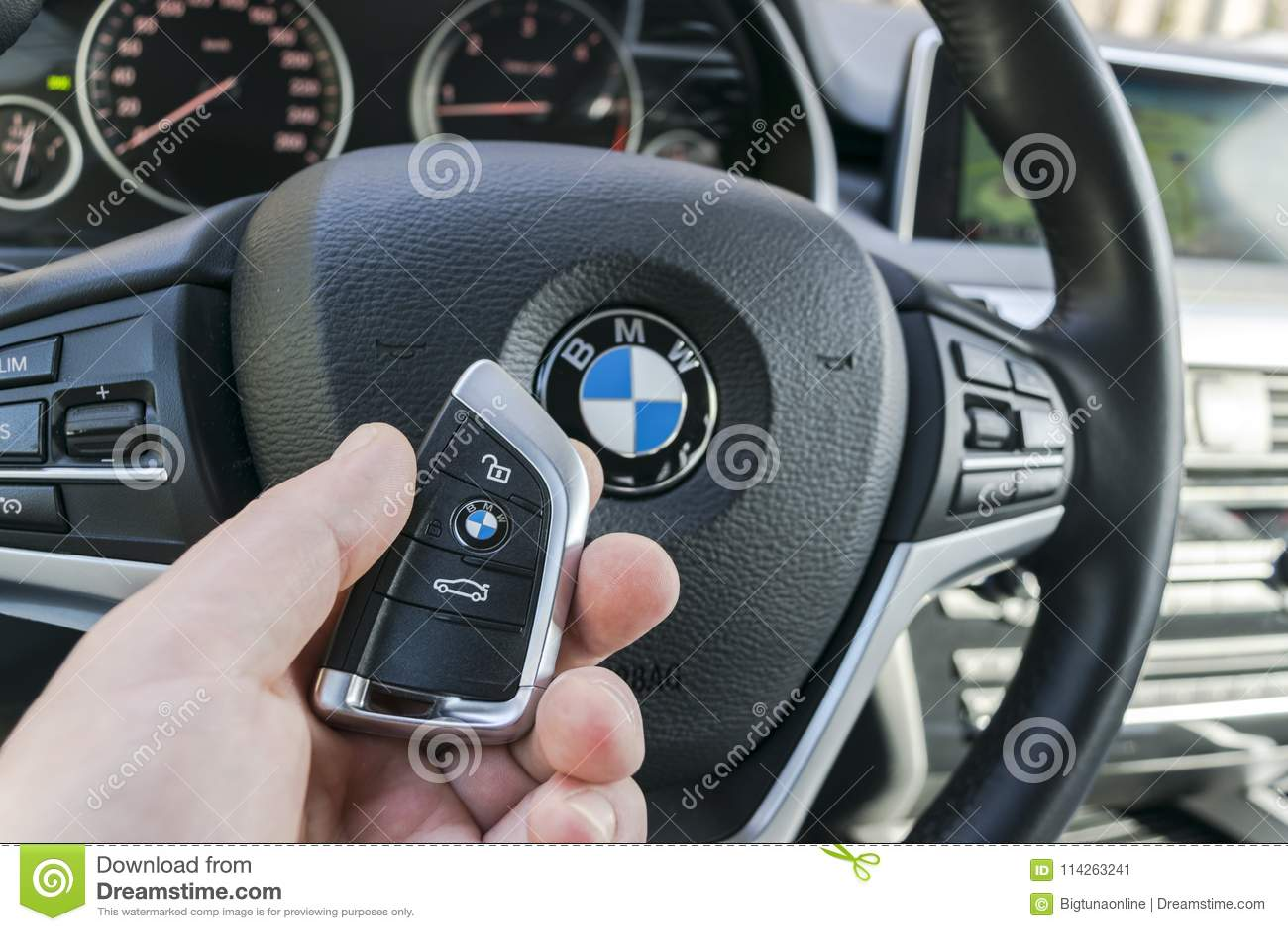 man`s hand holding a wireless bmw x5 f15 car key in black leather