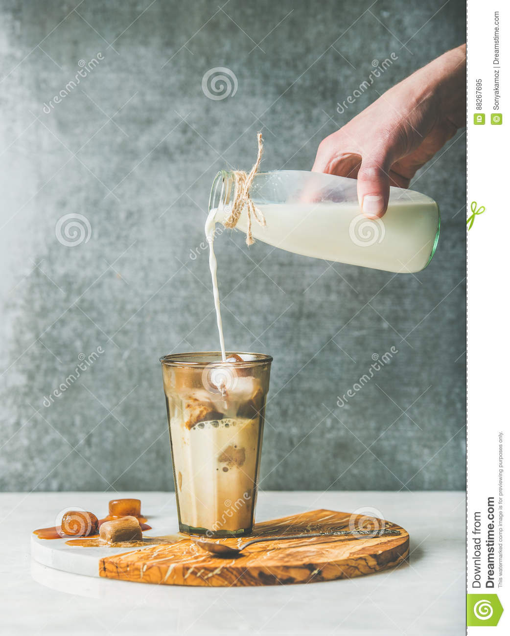 Man`s Hand Pouring Milk To Iced Latte Caramel Coffee