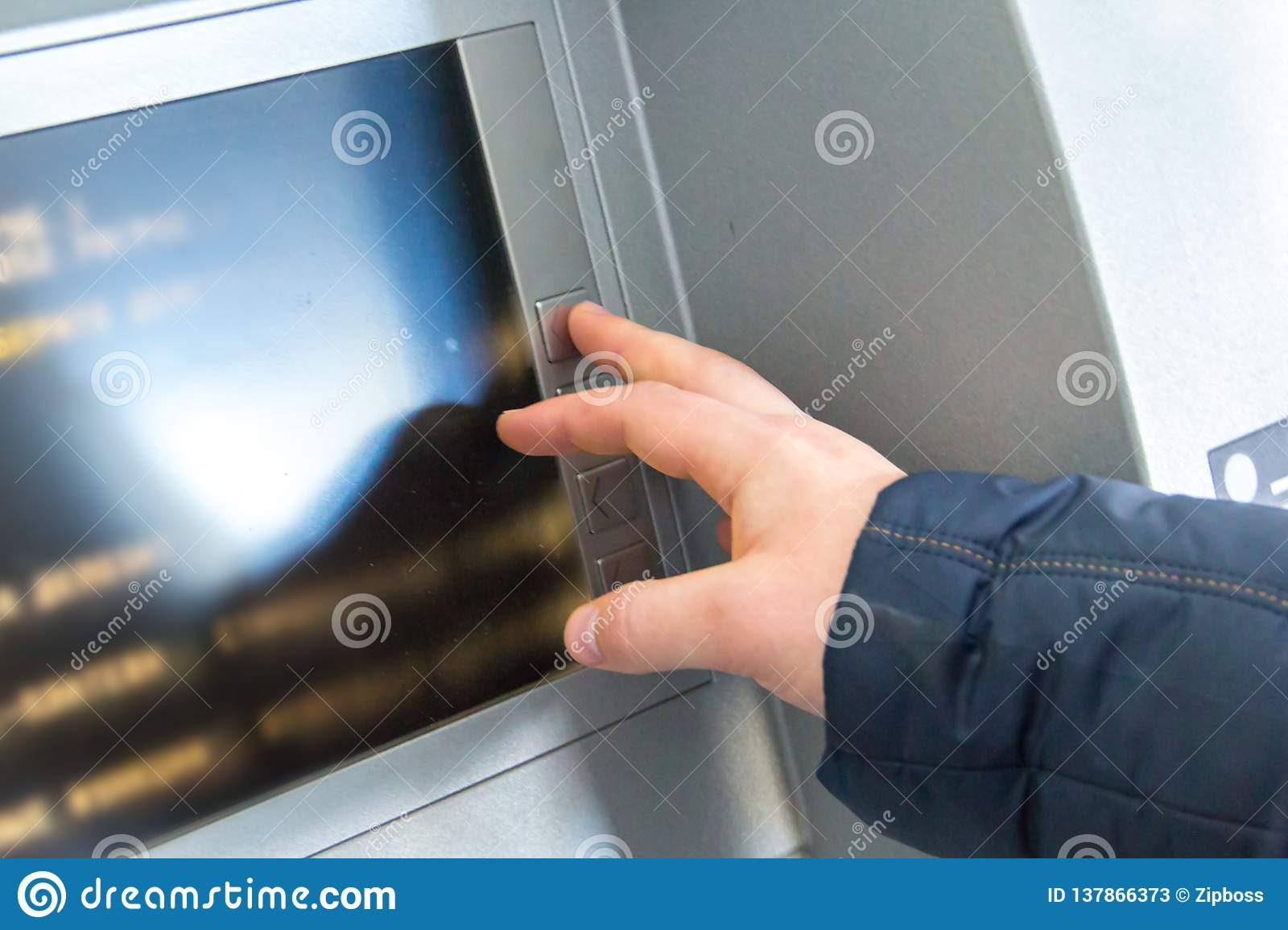 The man`s hand presses the buttons on the cash machine`s keyboard