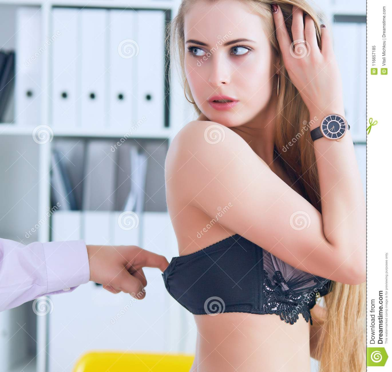 Man`s hand pulls bra out of the beauitiful secretary in office background. Flirt or harassment concept.