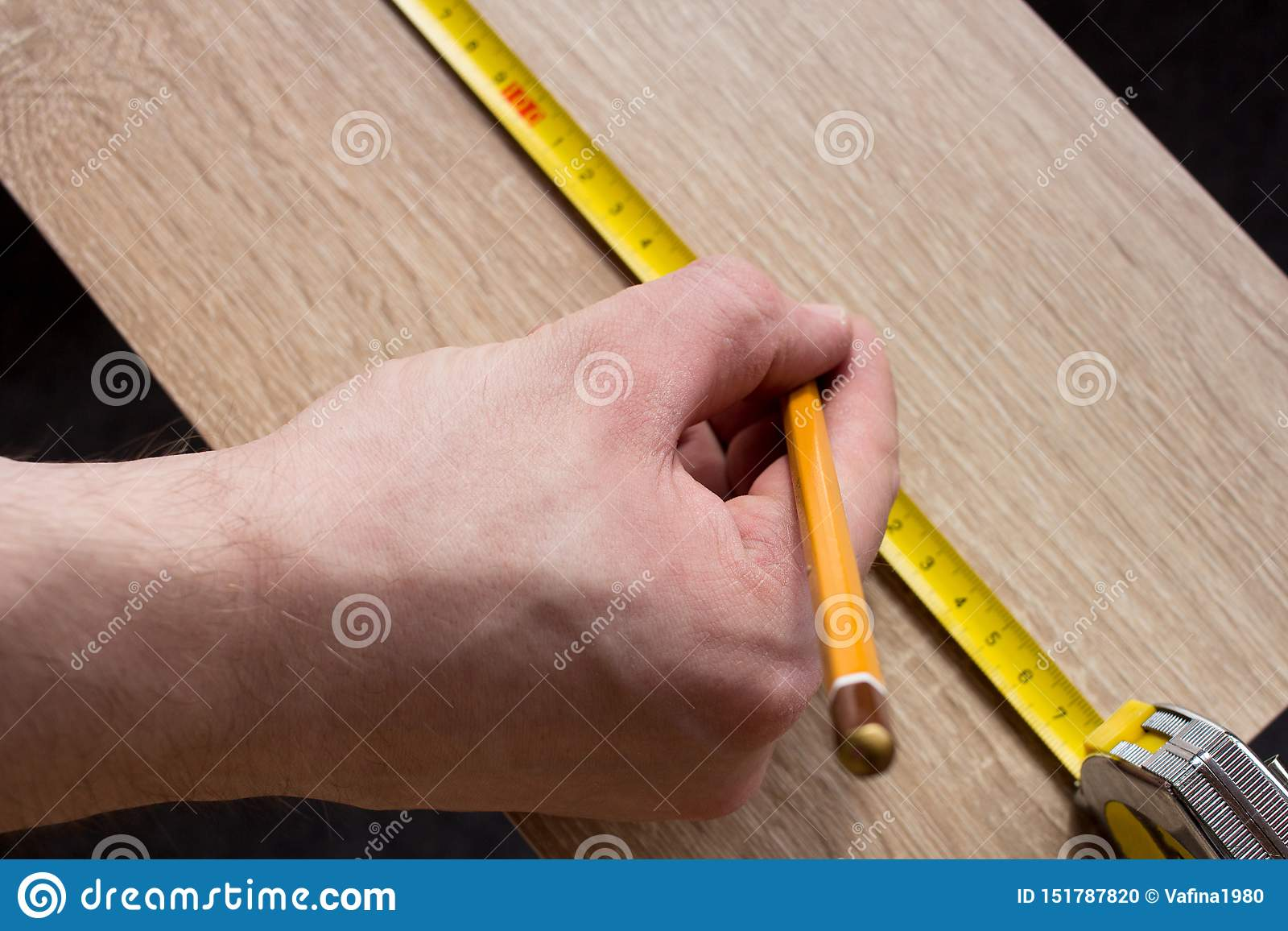 Man`s hands measuring wooden plank with a tape line