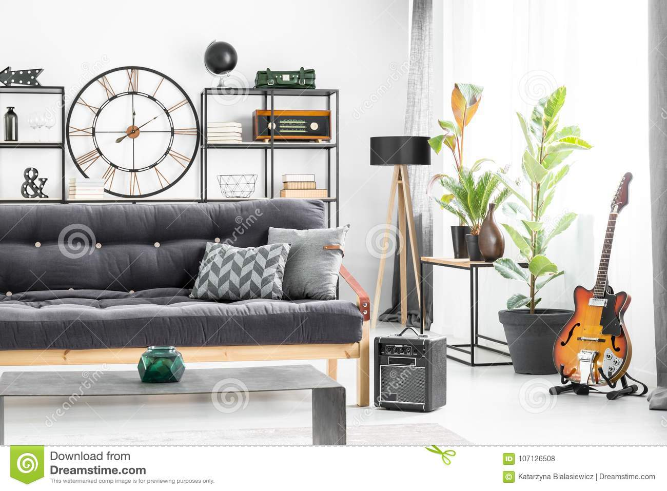 Grey Pillows On Dark Settee In Front Of A Table In Mans Living Room Interior With Guitar And Designer Clock On The Wall