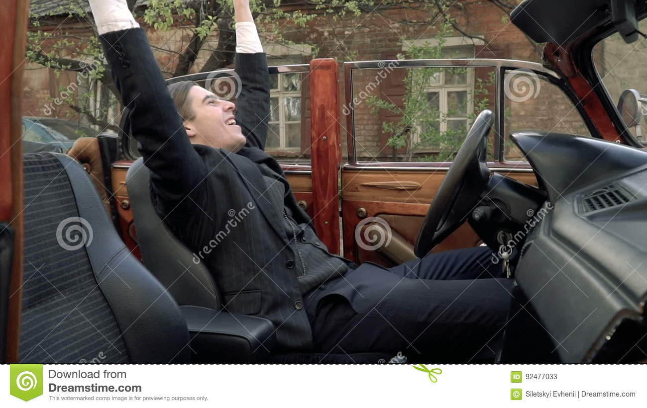 A Man In A 1920s Suit Rejoices In Something While Sitting At