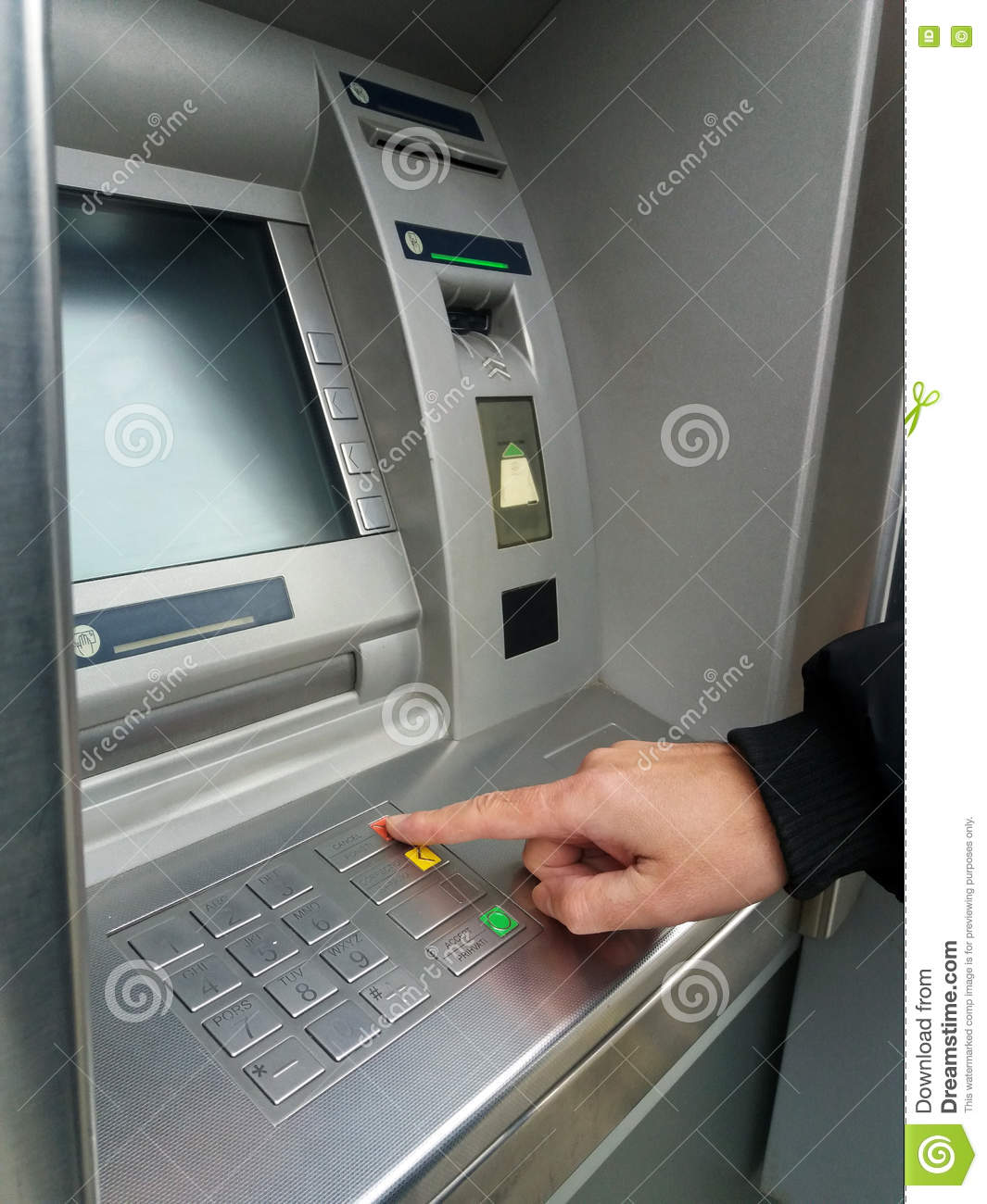 Man`s using the ATM machine with cash cards. Close-up of hand entering PIN/pass code on ATM/bank machine keypad.