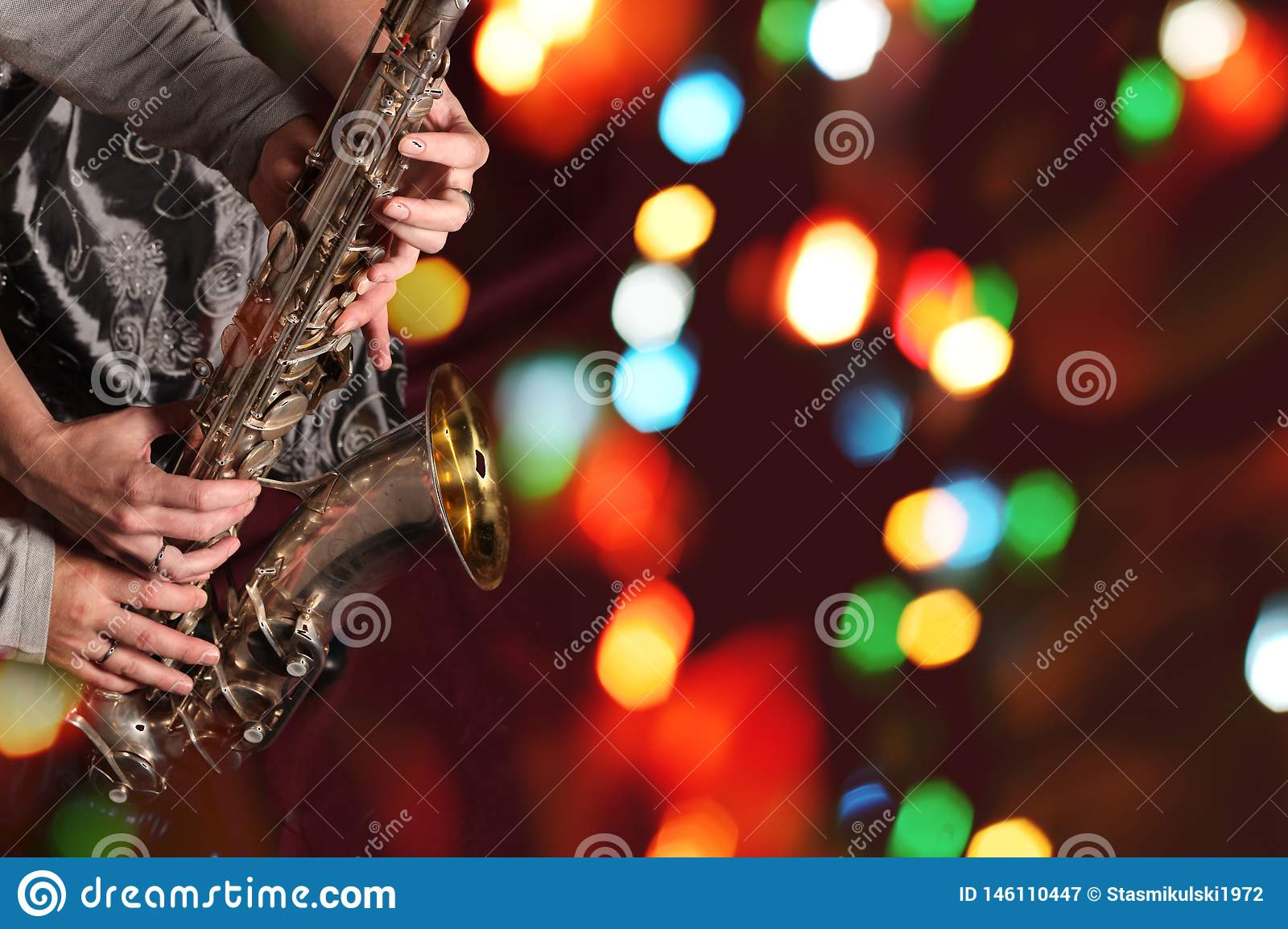 Man`s and woman`s hands with saxophone on bokeh lights