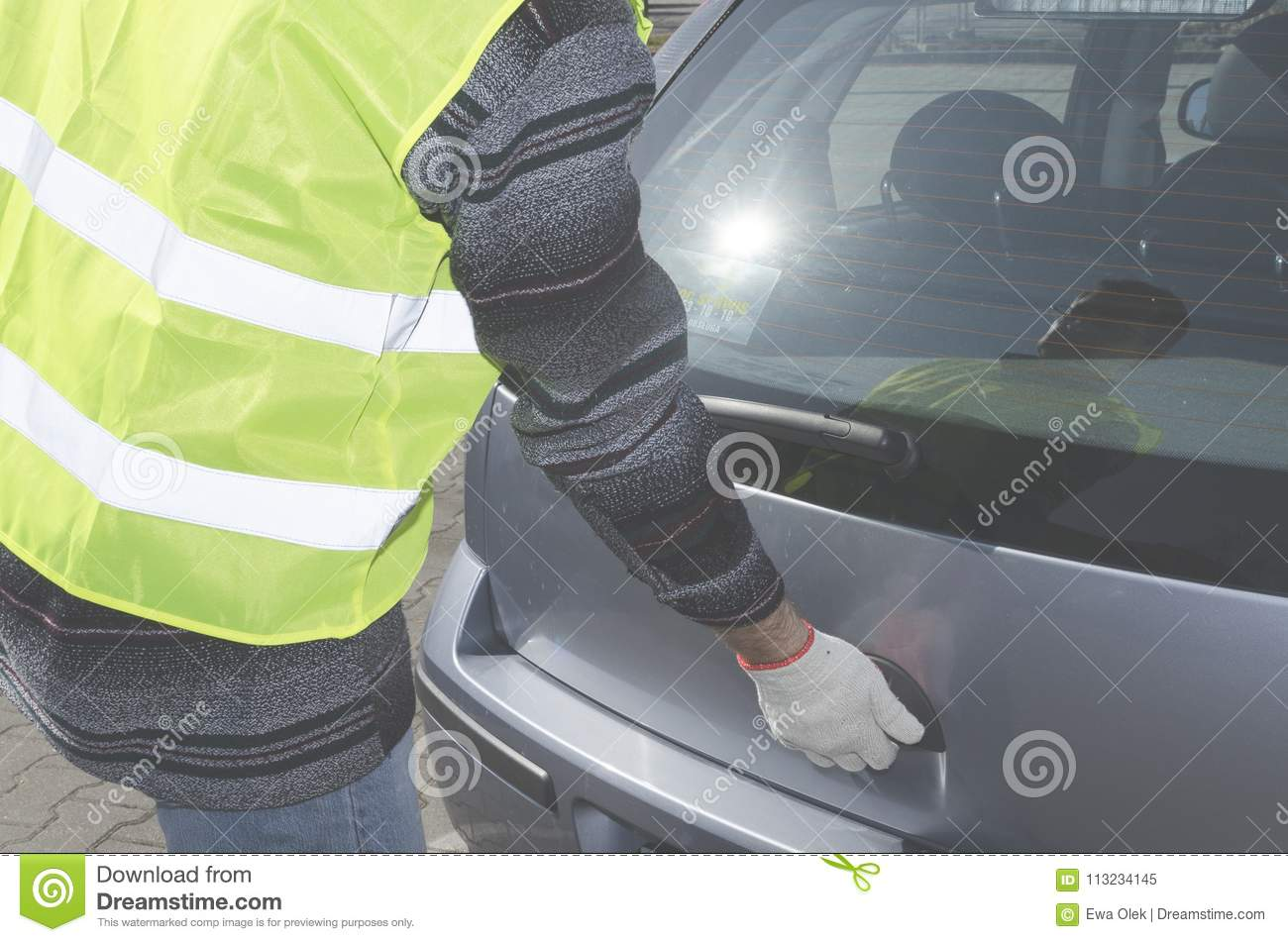 Man in a safety vest is opening boot in his car