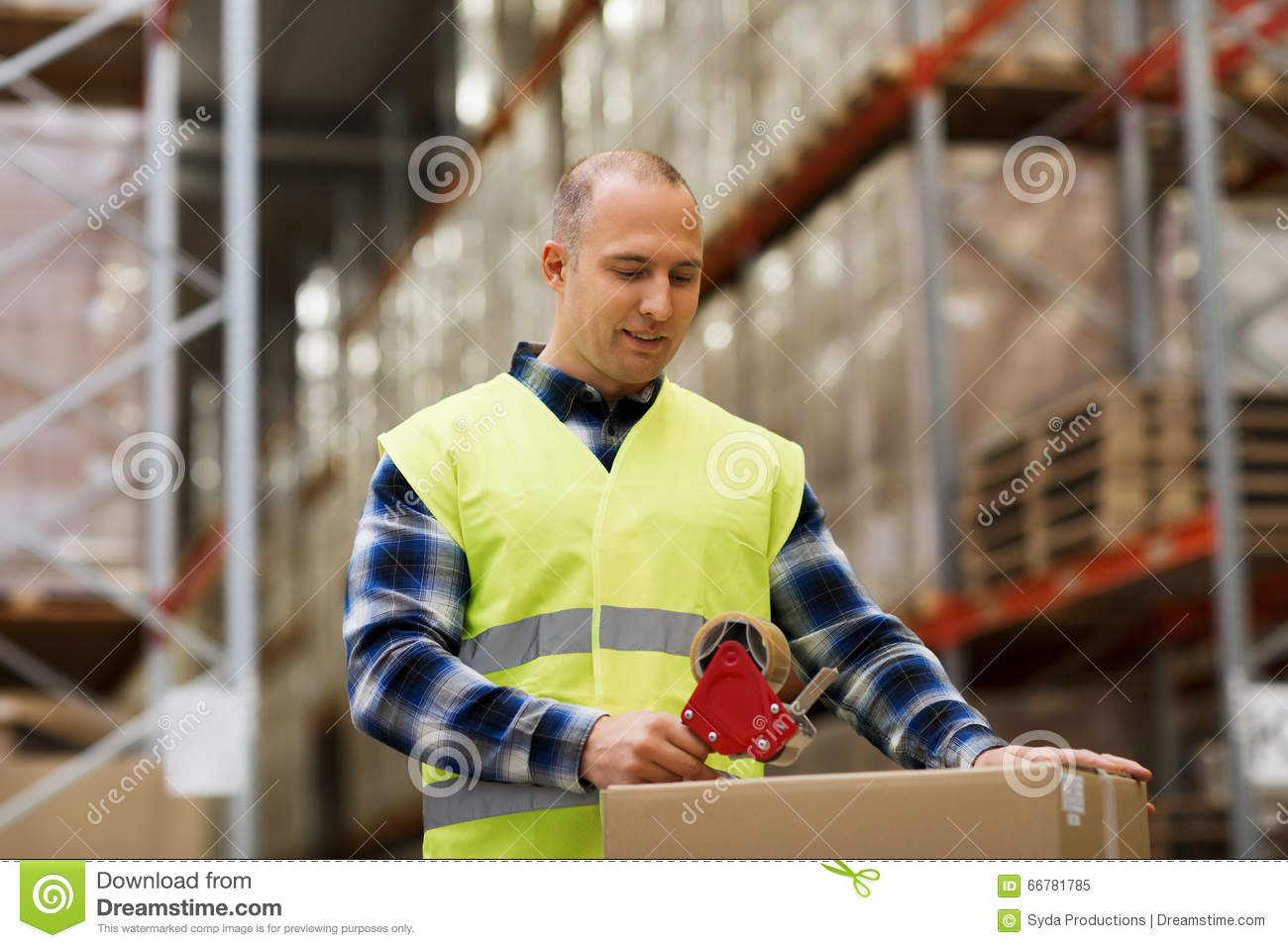Man in safety vest packing box at warehouse
