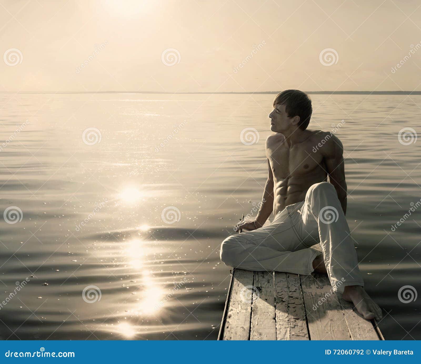 Man sammanträde på den lilla träbryggan på den soliga dagen för sommar