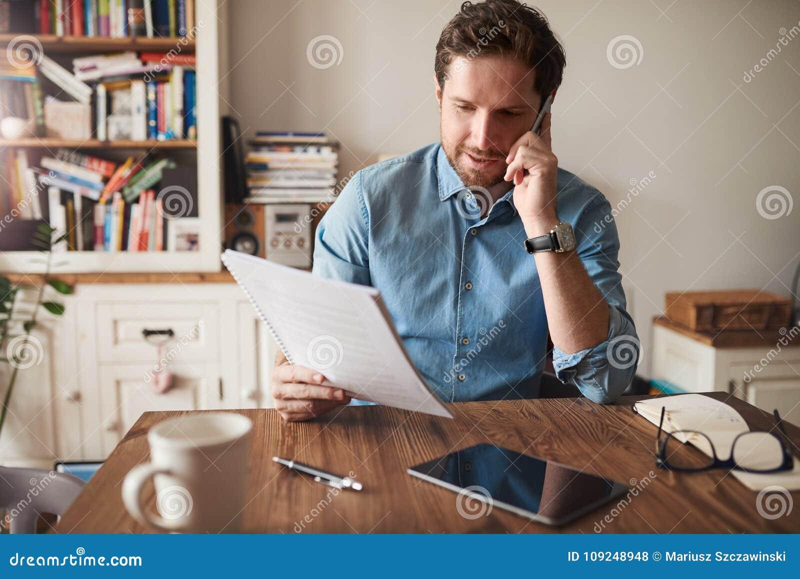 Man samtal på en mobiltelefon, medan läsa skrivbordsarbete hemma