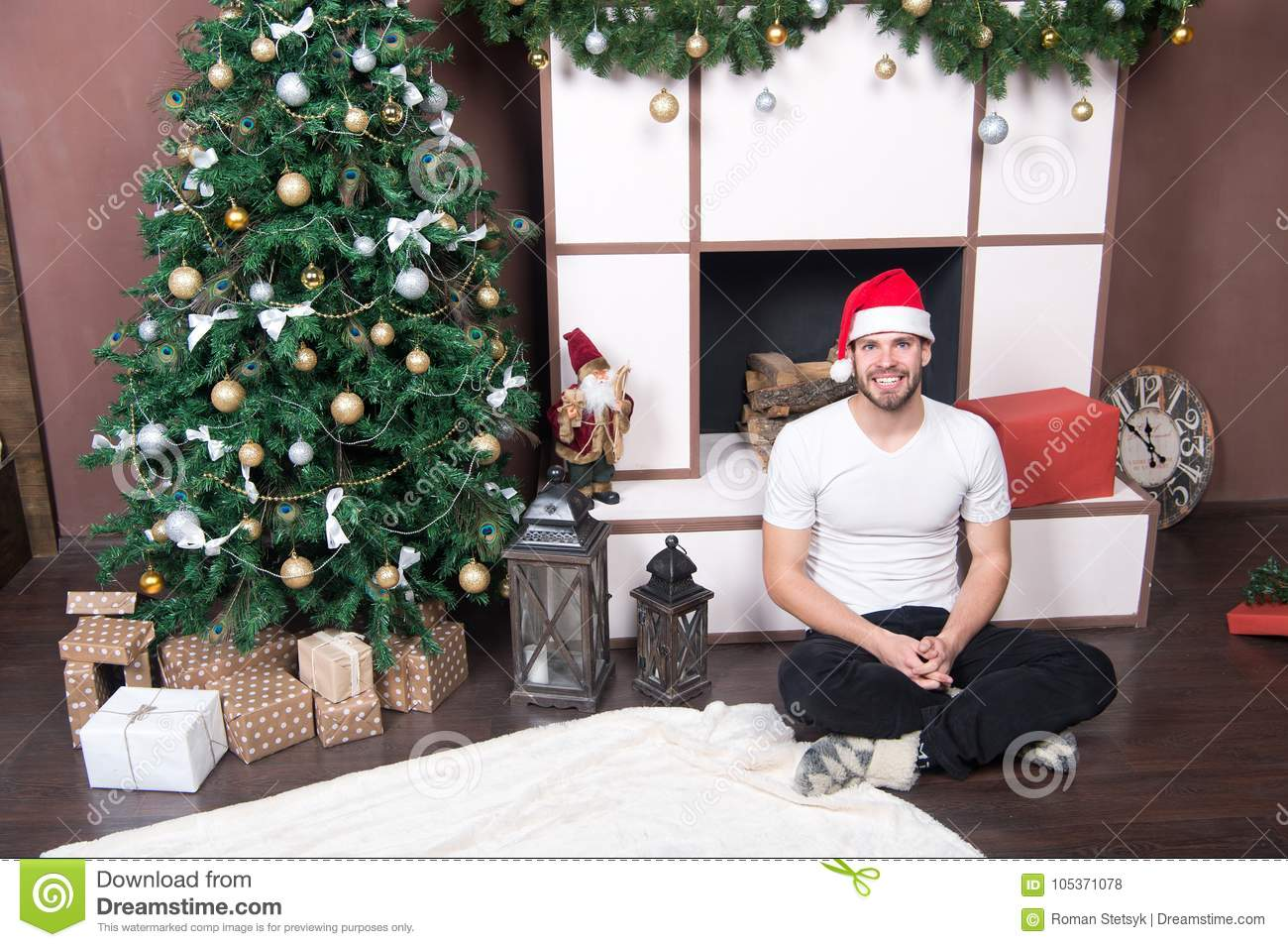 5fff7e1b91a2f Man in santa hat smile at fireplace. Macho sit at Christmas tree with present  boxes. xmas and new year room interior. Time to celebrate concept.