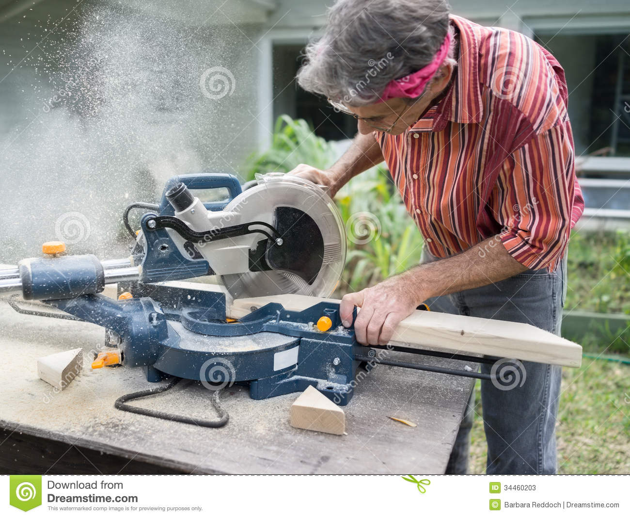 Man Sawing Wood With Sliding Compound Miter Saw Stock