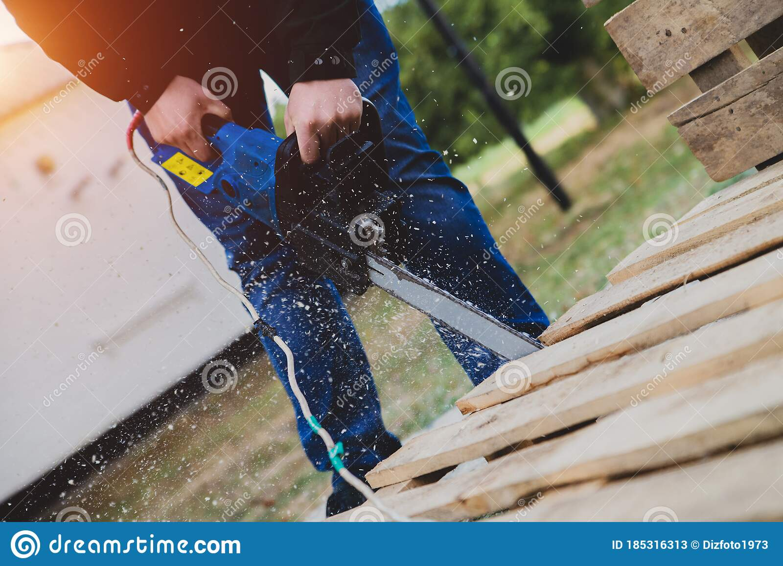 A Man Sawing A Wooden Pallet With A Chainsaw Making Outdoor Furniture From Pallets Stock Image Image Of Finishing Pallets 185316313