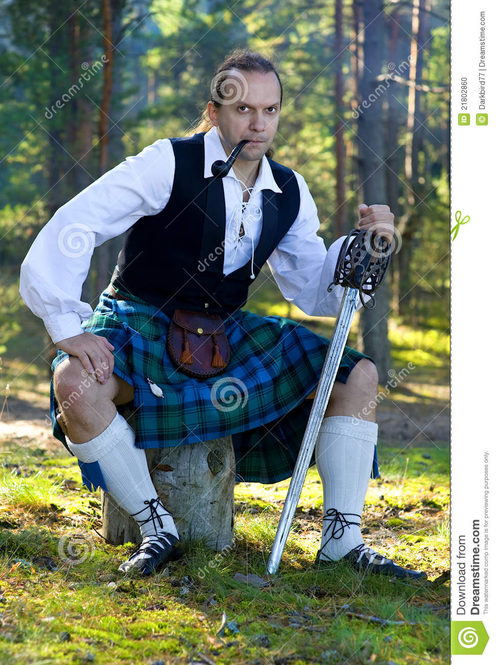 Man In Scottish Costume With Sword And Pipe Stock Photo