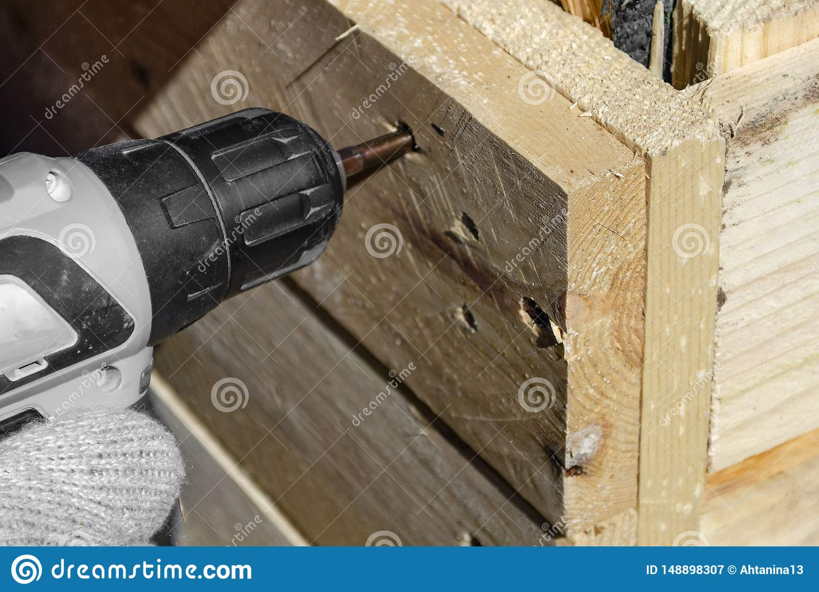 Experienced worker in a carpentry workshop creates a wooden product with raw boards and connects them with screws