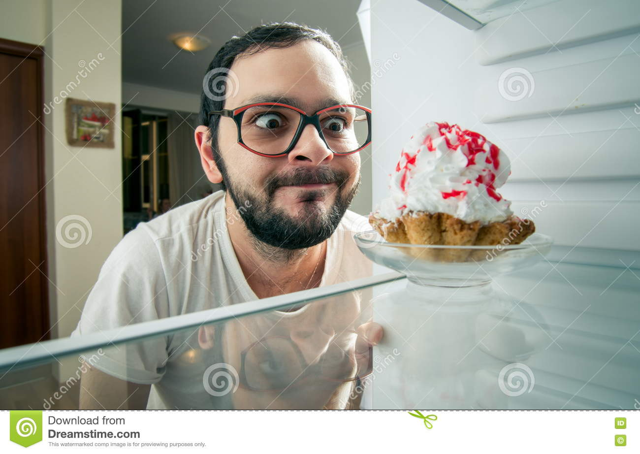 Man sees the sweet cake in the fridge