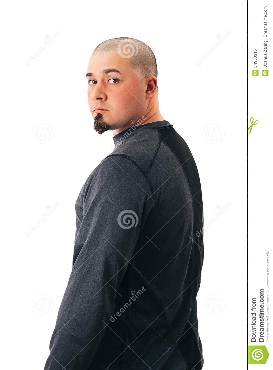 A fit, in shape man with a shaved head and goatee looking back. Isolated on  white.
