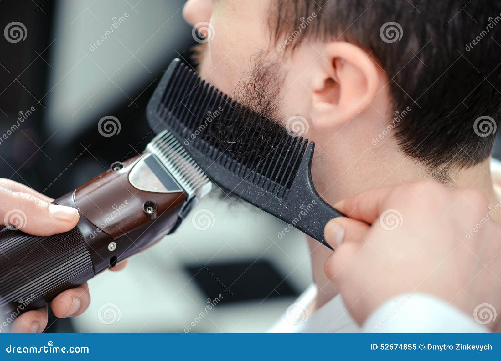 Man shaves his beard with a hair clipper
